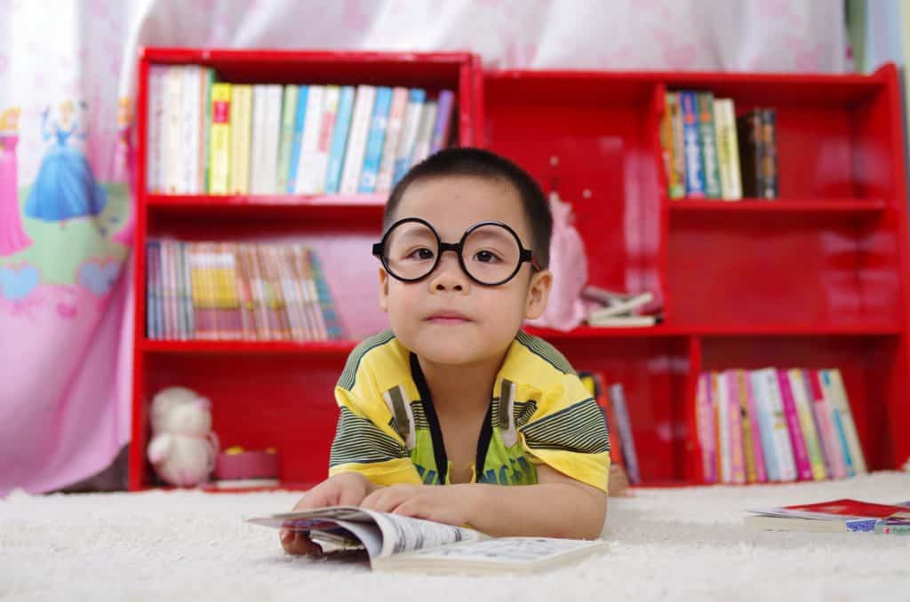 Boy with black circle glasses with a book