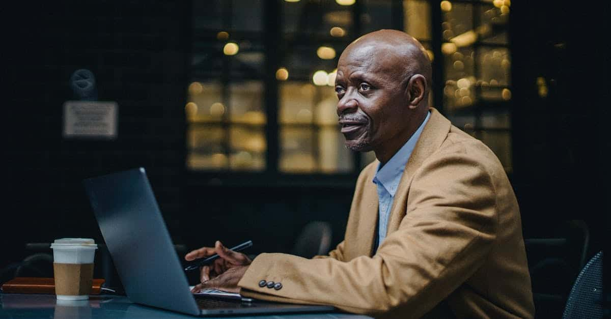 A man wearing a suit and tie sitting in front of a laptop