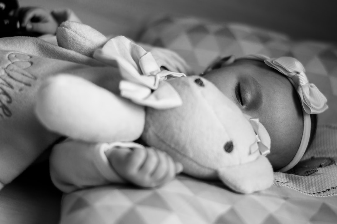 A baby lying on a bed with a teddy bear