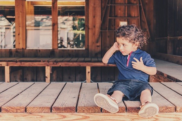 A young boy sitting on a bench