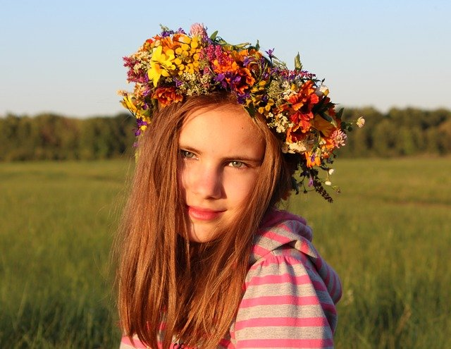 A close up of a girl with a flower in a field