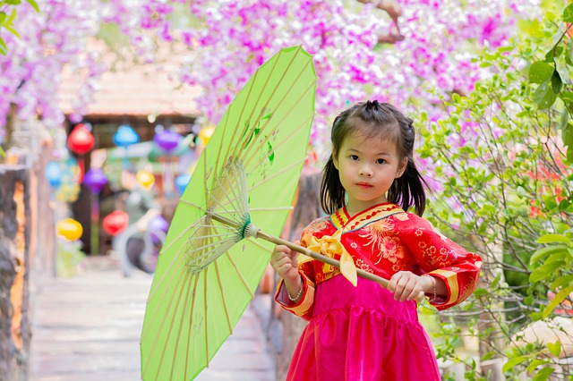 A little girl holding a colorful umbrella