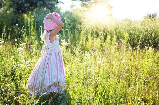 A girl standing in front of a tall grass field