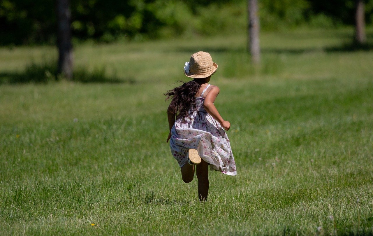 A young boy playing frisbee in a grassy field